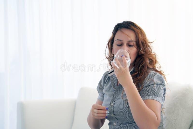 A mulher bebe um comprimido da dor fotografia de stock