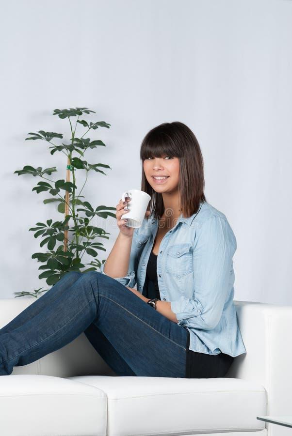 A mulher bebe uma xícara de café imagem de stock