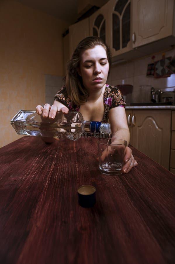A mulher bebida só derrama o álcool no vidro imagem de stock royalty free