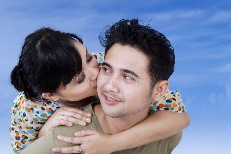 A mulher beija seu noivo no céu azul fotografia de stock