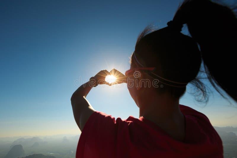 A mulher bem sucedida entrega a fatura de uma forma do coração na parte superior da montanha do nascer do sol imagem de stock royalty free
