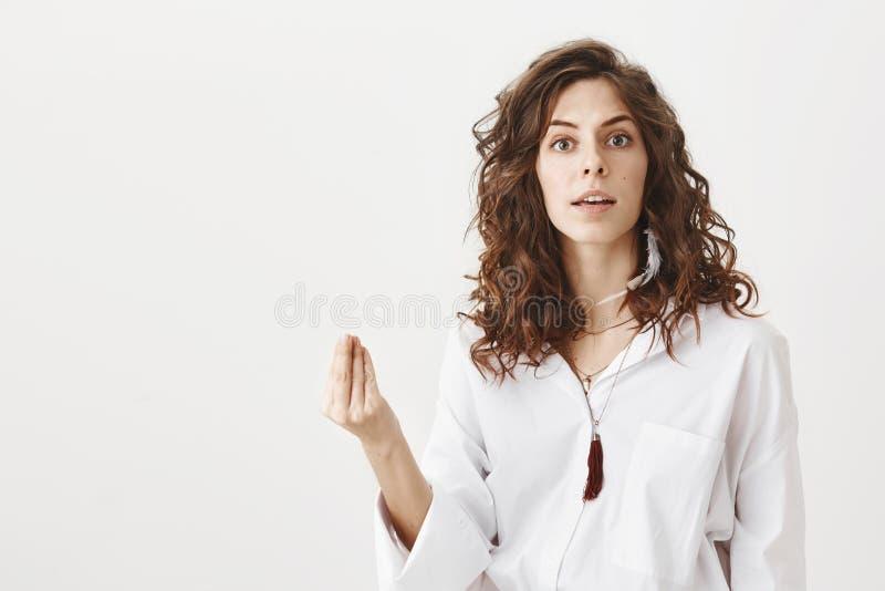 Mulher bem sucedida irritada e séria que mostra o italiano o que você querem o gesto, sendo incomodado por alguém ao estar foto de stock royalty free