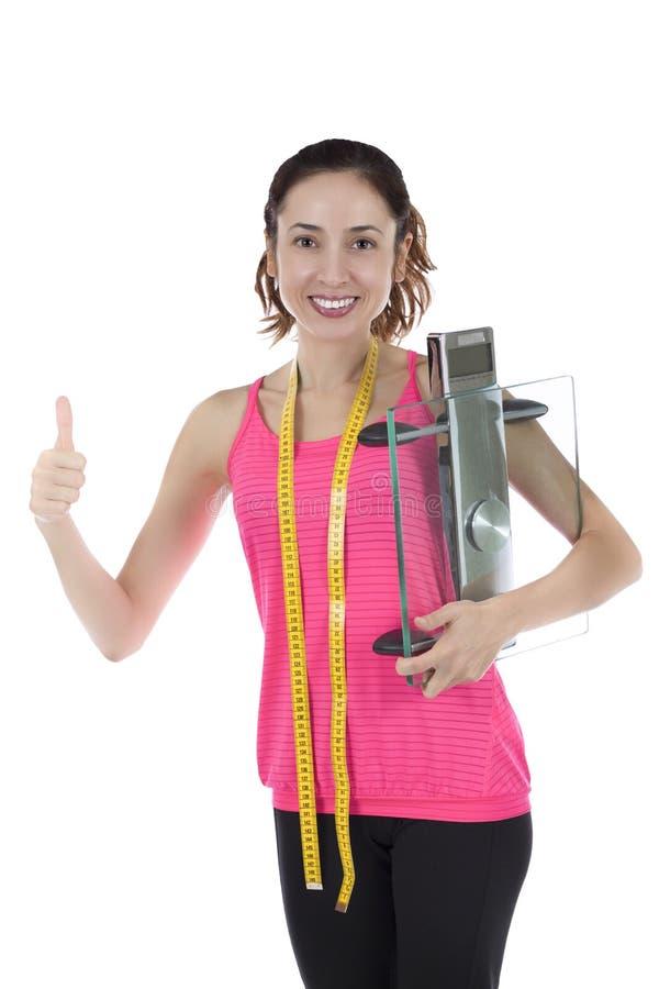Mulher bem sucedida na perda de peso que guarda uma escala de vidro fotografia de stock