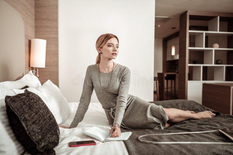 Mulher bem sucedida ocupada que sente o planeamento pensativo seu dia fotografia de stock