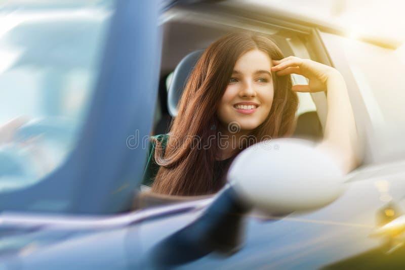 Mulher beuatiful nova que conduz um carro imagem de stock