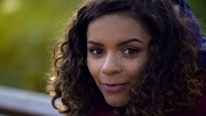 Mulher biracial bonita que levanta para a câmera e que sorri sinceramente, close-up da cara imagens de stock