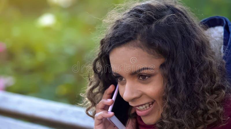 Mulher biracial encaracolado que fala ativamente sobre o smartphone, conversação com amigo foto de stock