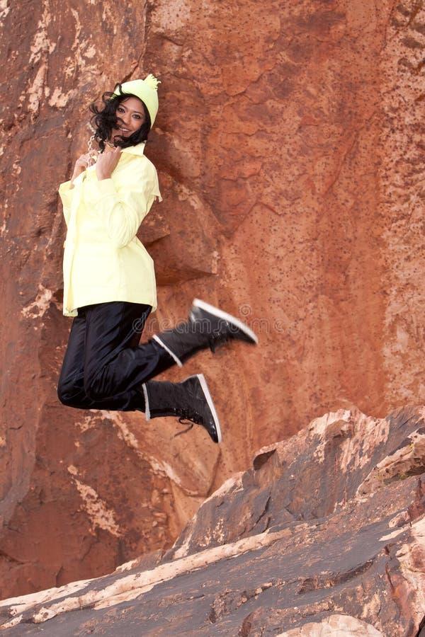 Mulher biracial nova no salto do raincoat imagens de stock