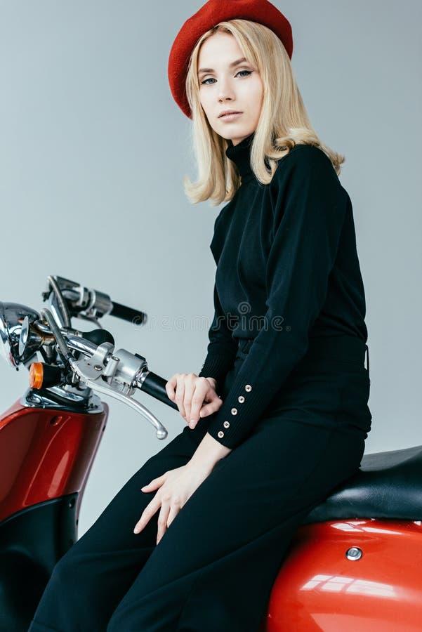 Mulher bonita à moda na roupa preta que levanta pelo 'trotinette' do vintage fotografia de stock royalty free