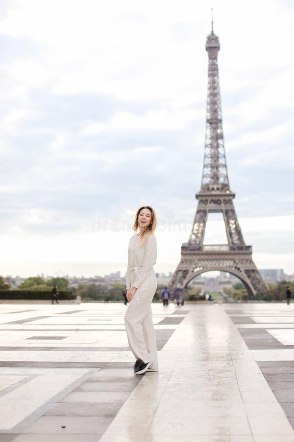 Mulher bonita à moda que está a torre Eiffel próxima nos macacões brancos foto de stock royalty free