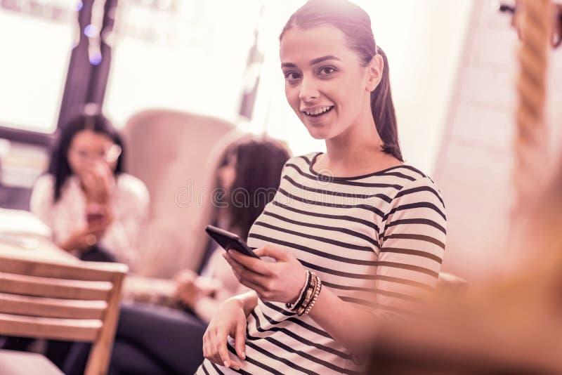 Mulher bonita à moda que veste braceletes agradáveis em seu smartphone da terra arrendada da mão fotografia de stock