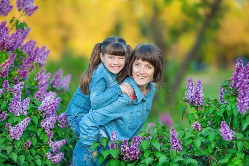 Mulher bonita adorável bonito da mamã da senhora da mãe com a filha moreno da menina no prado do arbusto roxo lilás Povos no desg fotografia de stock royalty free