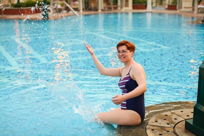 Mulher bonita adulta que faz a água espirrar na associação Apreciando o verão Humor das férias fotos de stock royalty free