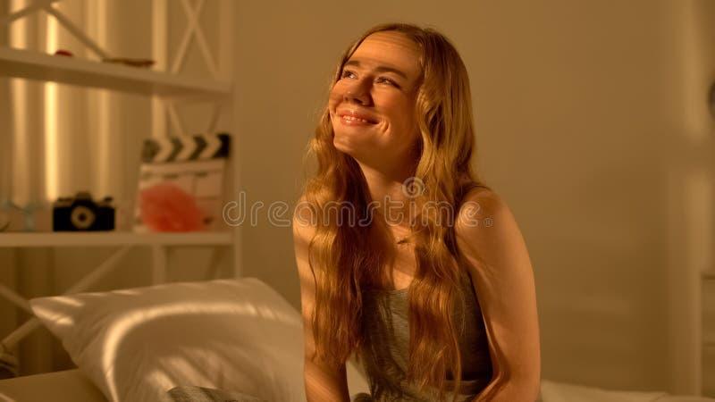 A mulher bonita alegre que senta-se em seja e que sorri, pensando sobre o sonho, felicidade fotos de stock