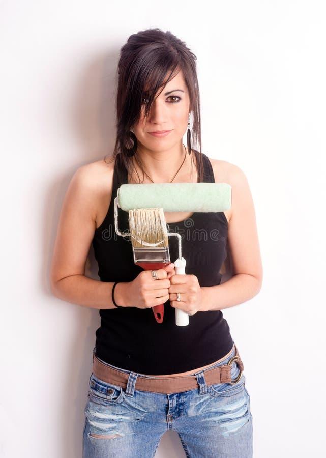 Mulher bonita anca que guarda o rolo da escova das ferramentas da pintura fotografia de stock royalty free