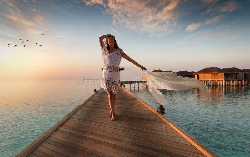 A mulher bonita anda abaixo de um molhe de madeira em Maldivas fotos de stock