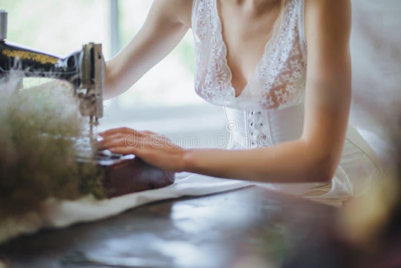 Mulher bonita Ao estilo de Coco Chanel que senta-se em uma máquina de costura fotos de stock