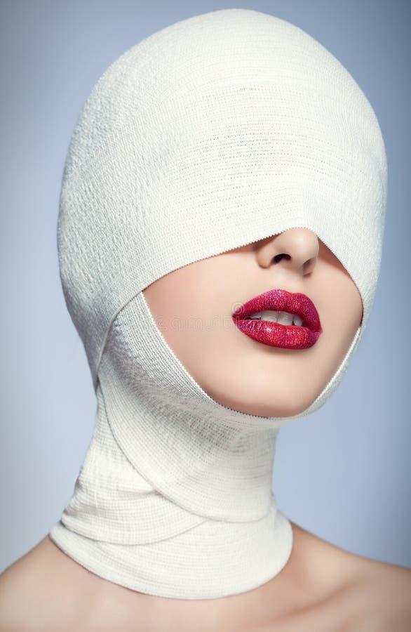 Mulher bonita após a cirurgia plástica com cara enfaixada foto de stock