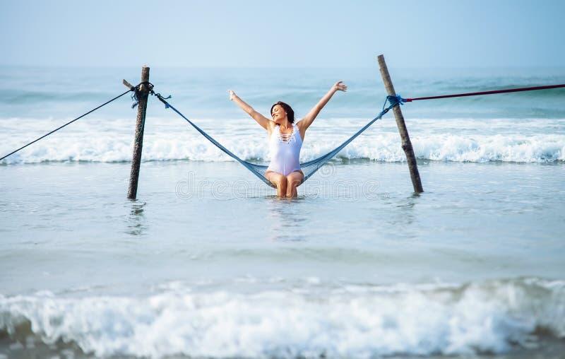 A mulher bonita aprecia com brisa do oceano e o sol senta-se no swi da rede fotografia de stock