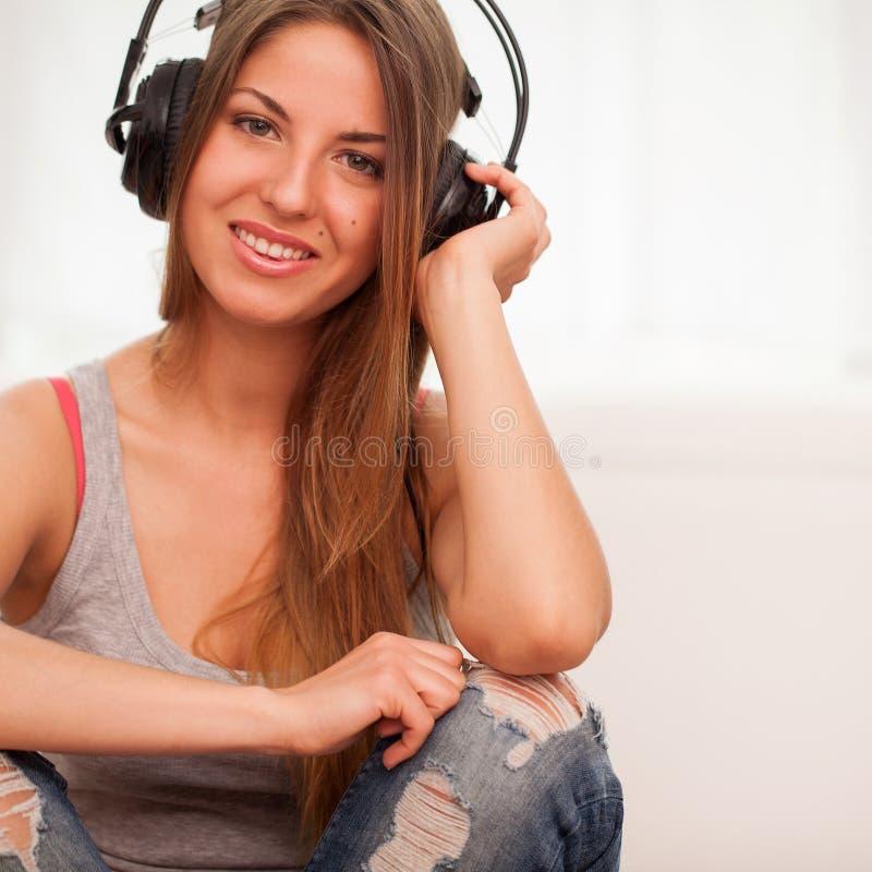 A mulher bonita aprecia a música nos fones de ouvido imagem de stock
