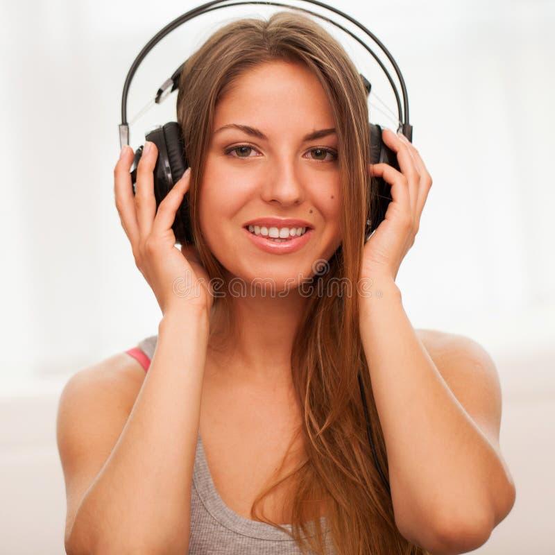 A mulher bonita aprecia a música nos fones de ouvido fotografia de stock royalty free