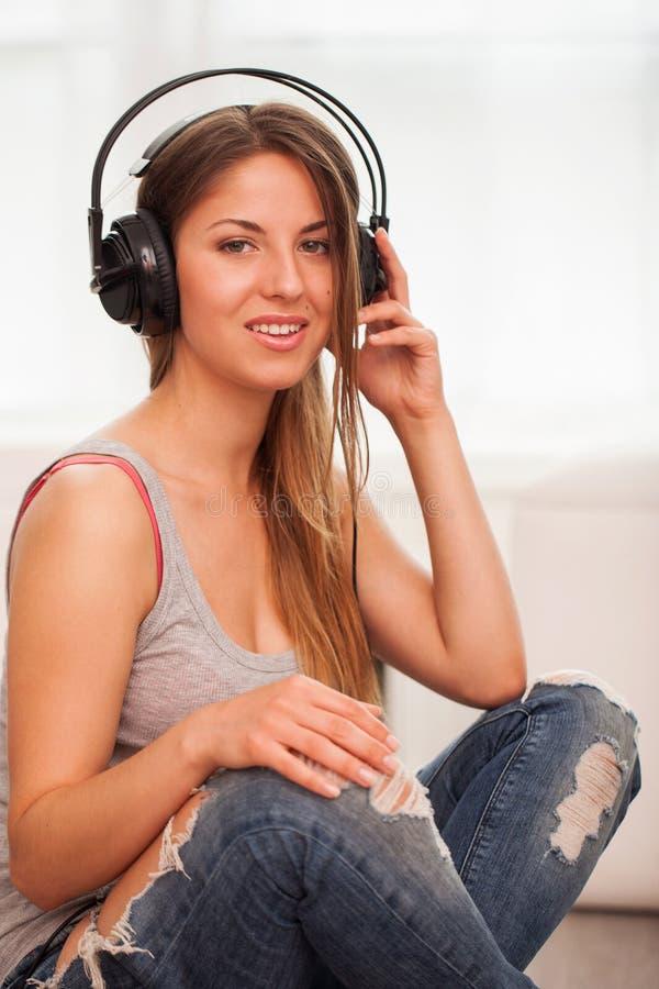 A mulher bonita aprecia a música nos fones de ouvido fotografia de stock