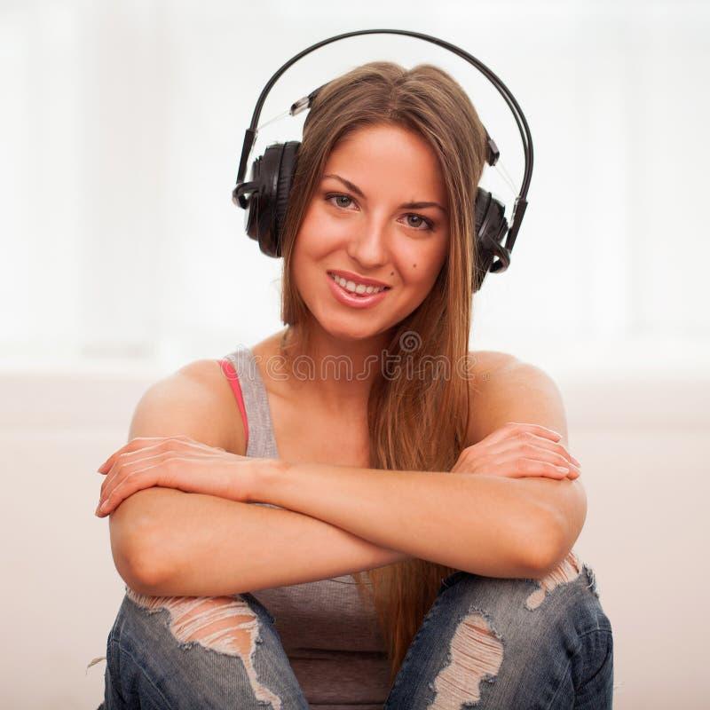 A mulher bonita aprecia a música nos fones de ouvido imagens de stock