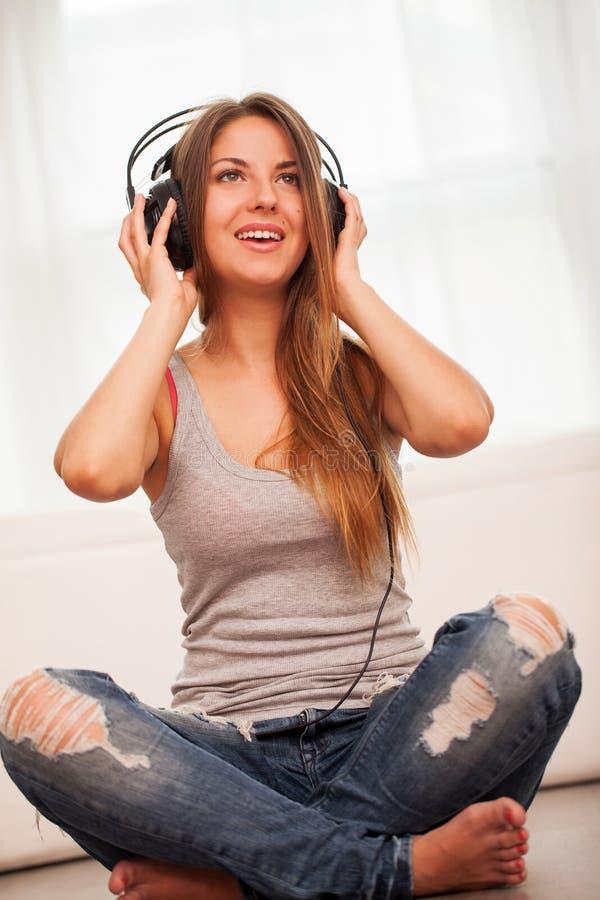 A mulher bonita aprecia a música nos fones de ouvido foto de stock