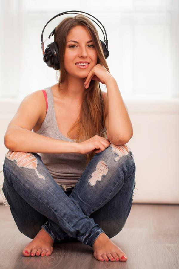 A mulher bonita aprecia a música nos fones de ouvido foto de stock royalty free
