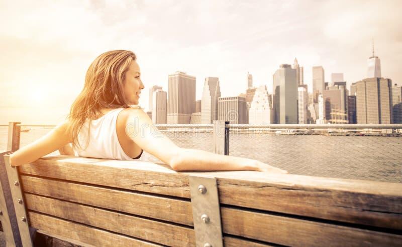 A mulher bonita aprecia a skyline de New York fotografia de stock