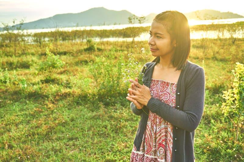 A mulher bonita asiática é de sorriso e de doação um ramalhete das flores fotografia de stock