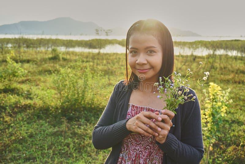 A mulher bonita asiática é de sorriso e guardando um grupo de flores selvagens minúsculas em sua mão foto de stock royalty free