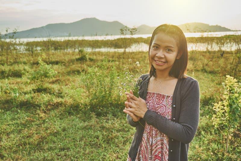 A mulher bonita asiática é de sorriso e guardando um grupo de flores selvagens minúsculas em sua mão imagens de stock