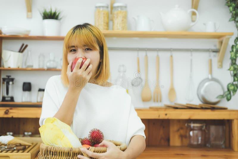 A mulher bonita asiática come a maçã vermelha na cozinha em sua casa A fêmea asiática bonita feliz come o fruto do frescor para o imagens de stock