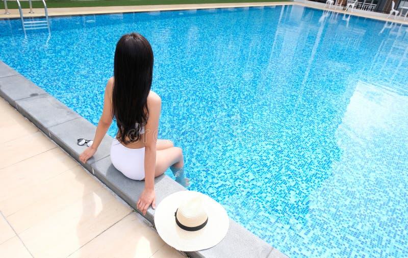 Mulher bonita asiática nova que relaxa na piscina fotografia de stock royalty free