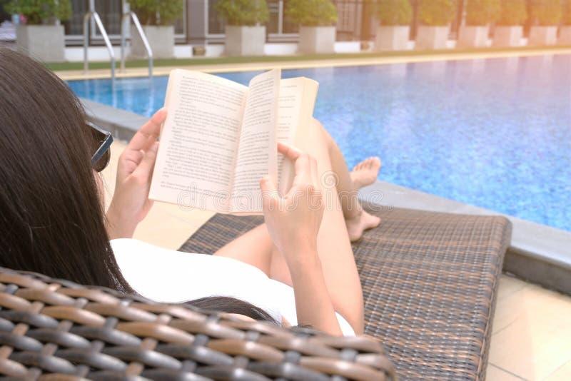 Mulher bonita asiática nova que relaxa na piscina que encontra-se na imagens de stock royalty free