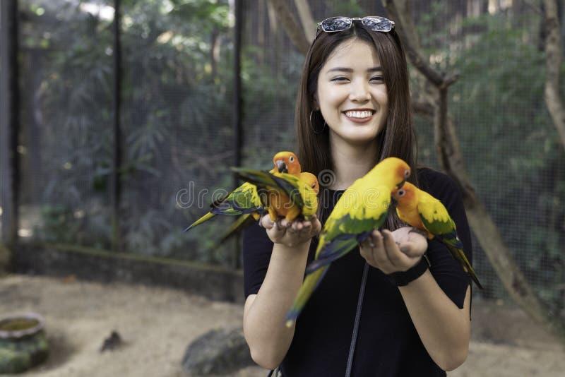 Mulher bonita asiática que aprecia com pássaro do amor disponível e corpo fotografia de stock royalty free
