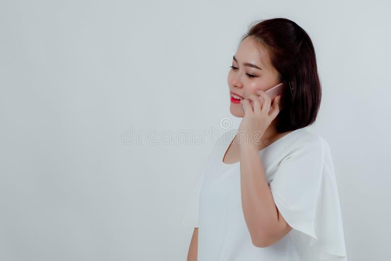 A mulher bonita asiática que está em uma camisa branca pôs o telefone celular unido à orelha para falar ao destino Prepare a foto de stock