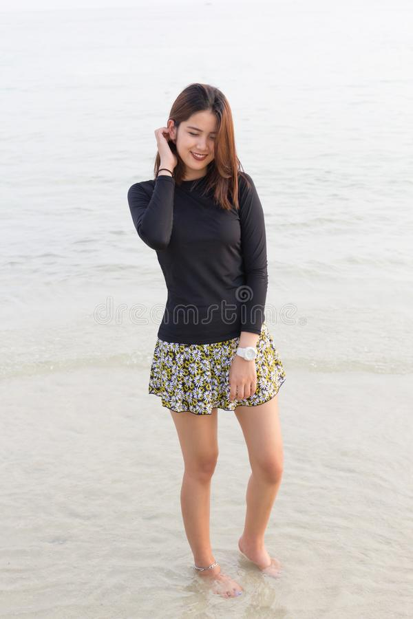 A mulher bonita asiática relaxa no fundo da praia foto de stock