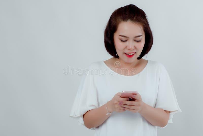 A mulher bonita asi?tica que est? em uma imprensa branca do suporte do telefone celular da camisa prepara-se para fazer uma chama foto de stock