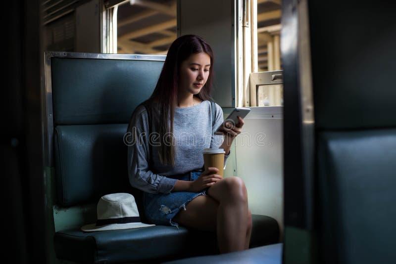 A mulher bonita atrativa de Ásia é de jogo ou procurar algum lugar que quer ir lá durante o trem está estacionando no tra imagens de stock royalty free