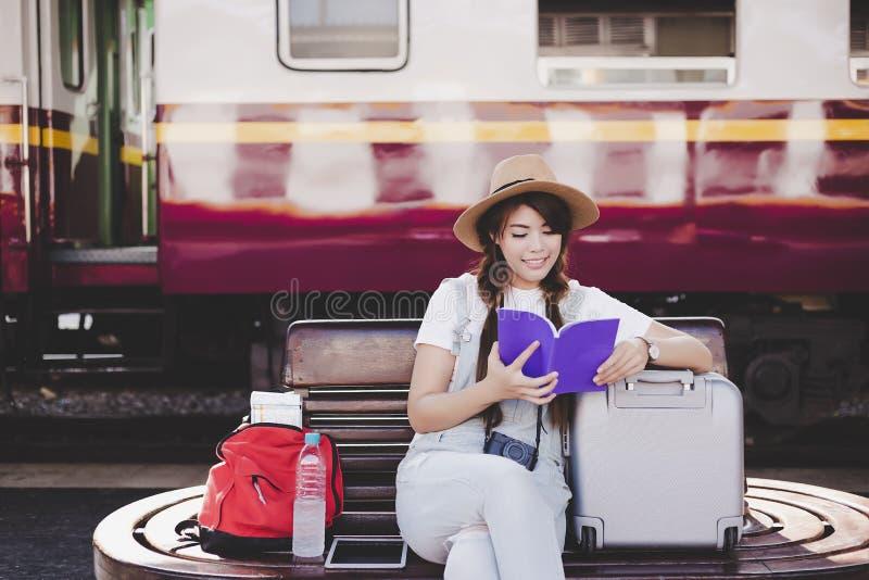 A mulher bonita atrativa do turista está lendo o guia de curso imagem de stock