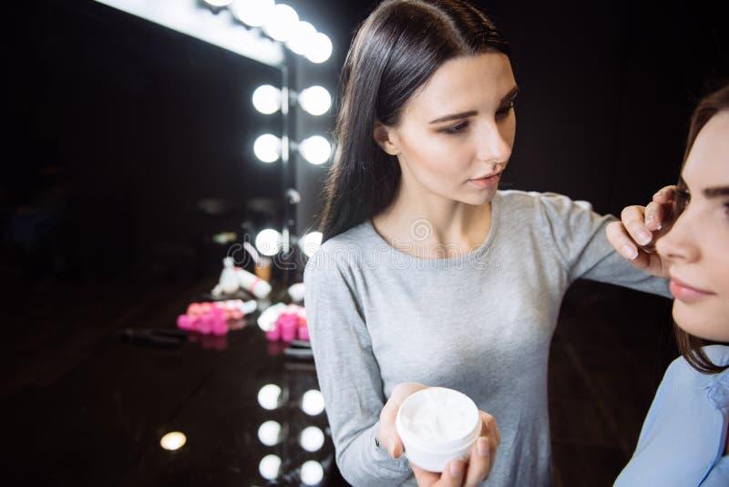 Mulher bonita atrativa que aplica o creme em sua cara dos clientes imagem de stock