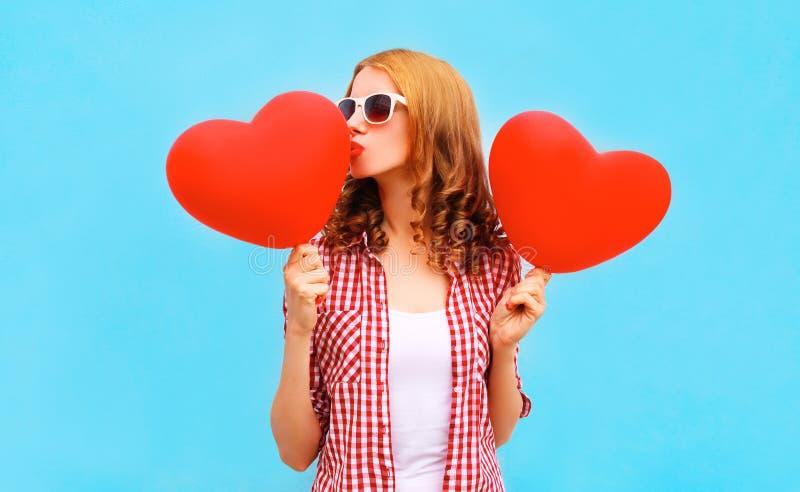 A mulher bonita beija um balão de ar vermelho na forma de um coração imagem de stock