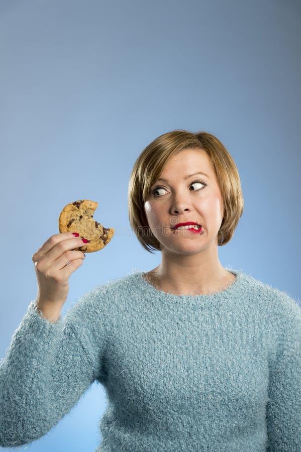Mulher bonita bonito com mancha do chocolate na boca que come a cookie deliciosa grande foto de stock