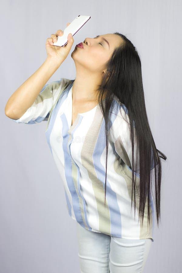 Mulher bonita bonito na camisa que atua de jogo no telefone Isolado no fundo cinzento fotografia de stock