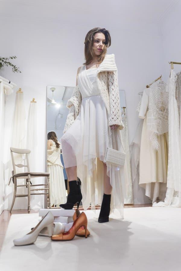 A mulher bonita cabe em um vestido branco no shopping em uma oficina foto de stock royalty free