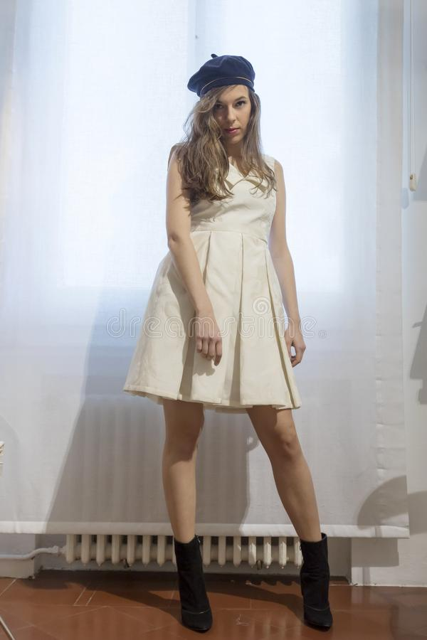 A mulher bonita cabe em um vestido branco no shopping em uma oficina imagens de stock royalty free