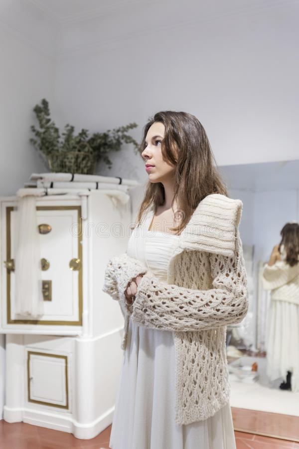A mulher bonita cabe em um vestido branco no shopping em uma oficina imagem de stock