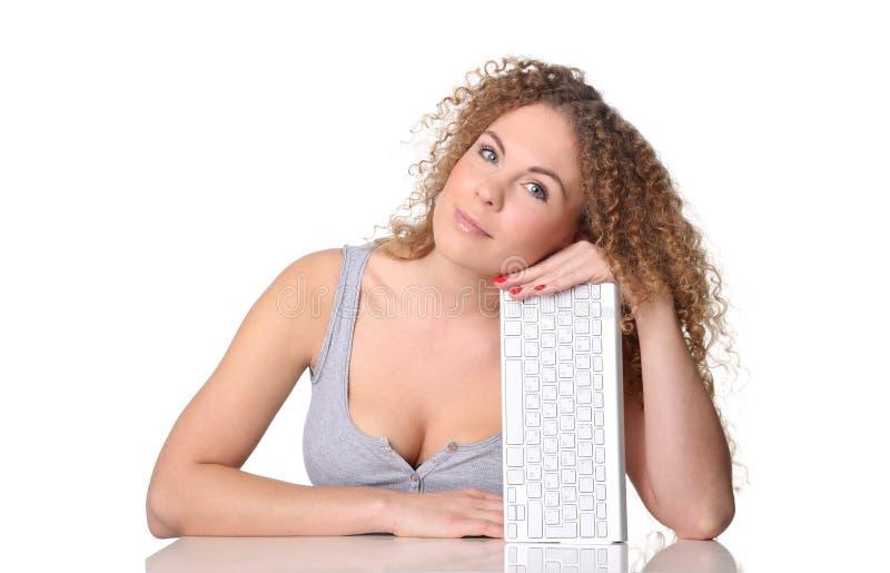 Mulher bonita, cabelo encaracolado vermelho, sentando-se em uma mesa com teclado fotografia de stock royalty free